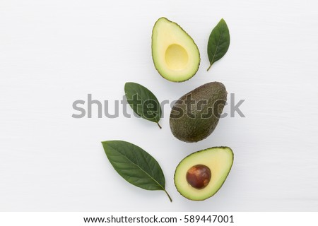 Slices of avocado on white background. Whole and half with leaves. Design element for product label. #589447001