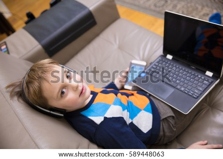 Little boy using a white  laptop computer at home along with mobile phone, wearing headphones, playing some games. #589448063