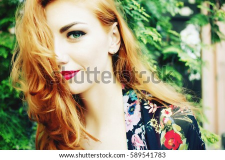 Closeup of beautiful red haired woman with matt red lips and eye makeup, eyeliner. Photo toned style instagram filters. Bohemian, bo-ho style, indie hippie, ring, bracelet.