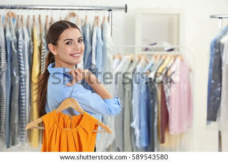 Female worker in dry-cleaning salon #589543580