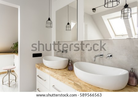 Minimalist bathroom with two sinks and wooden vanity top Royalty-Free Stock Photo #589566563