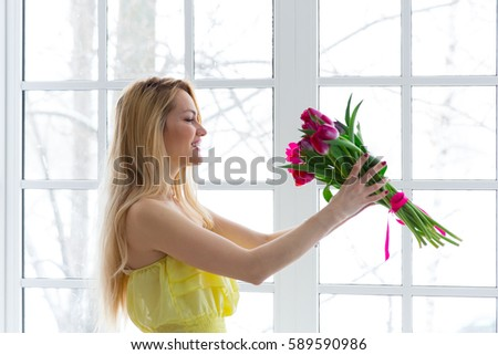 Young happy woman smiling with tulip bunch in yellow dress. 8 march international womens day #589590986