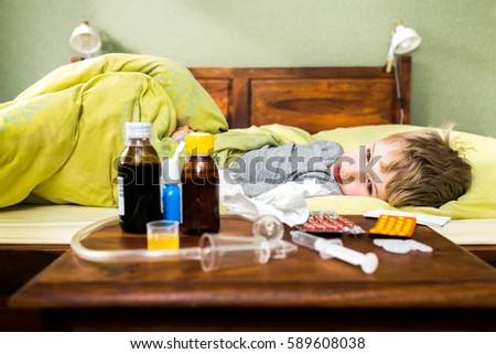 Sick child boy lying in bed, resting at home. #589608038