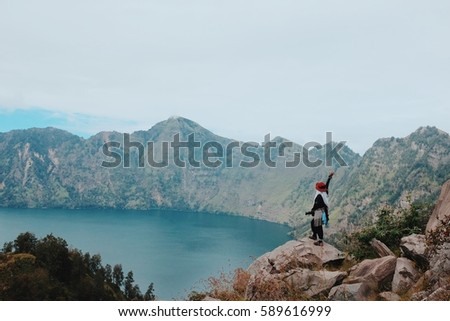 Mount Rinjani, INDONESIA - 4 September 2016: Girl looking at the lake of Mount Rinjani, Indonesia. #589616999