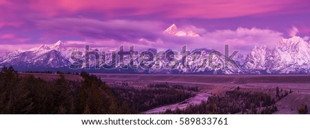 Panoramic view as dawn breaks with a purple glow revealing low clouds on the Teton mountains seen from the Snake River overlook in Grand Teton National Park, Wyoming