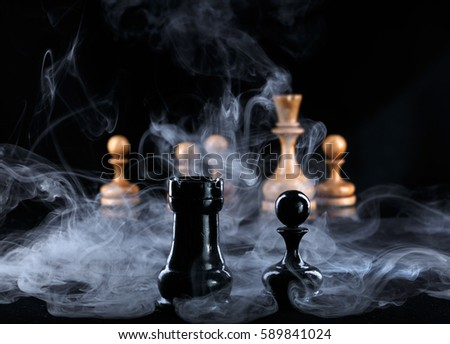 two black chess pieces in the fog opposite the white figures #589841024