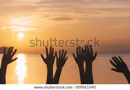 Many hands raised against sunset sky #589861040