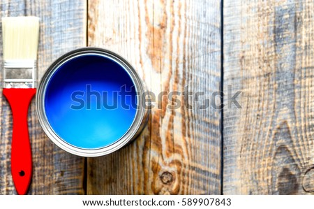 painting  with can blue paint on wooden background top view #589907843
