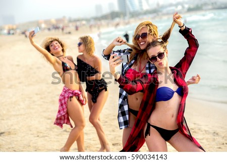 Young beautiful ladies having fun at beach taking pictures and looking happy enjoying summertime