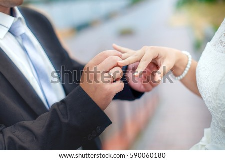 Groom wears bride a wedding ring on his finger. A couple betrothed in the street. Wedding ceremony - hands closeup. #590060180