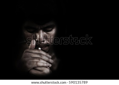 man lighting cigarette on black in white tone #590135789