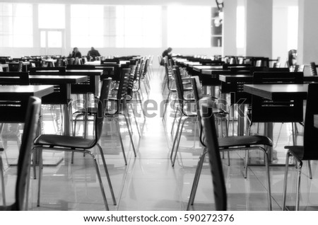 Blurred rows of wooden tables and plastic chairs in the restaurant, black and white #590272376