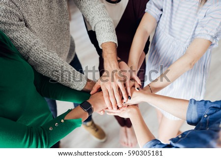 Cropped shot of a group of businesspeople piling their hands on top of each other #590305181