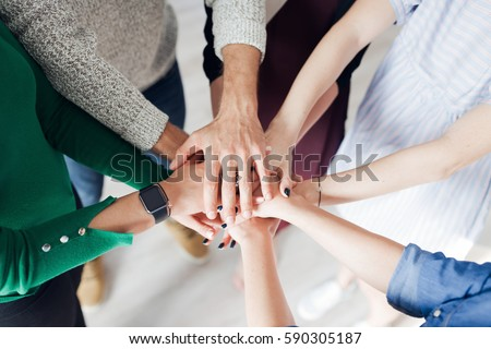 Top view of co-workers hand put together in an expression of unity and team spirit #590305187