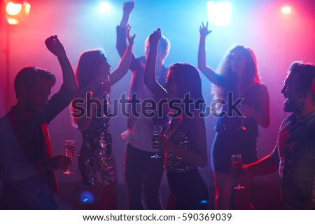 Happy students celebrating prom in night club, dancing with raised hands and holding glasses of champagne #590369039