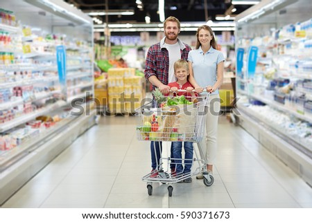 Bearded father, attractive mother and their little son posing for photo with wide smiles while shopping in hypermarket #590371673