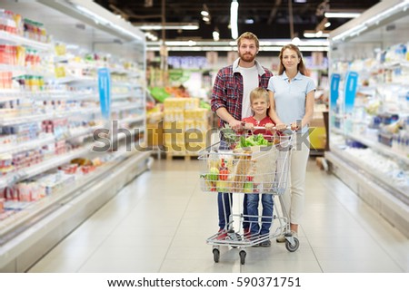 Full-length portrait of confident young family with little son standing in supermarket and holding full shopping cart #590371751