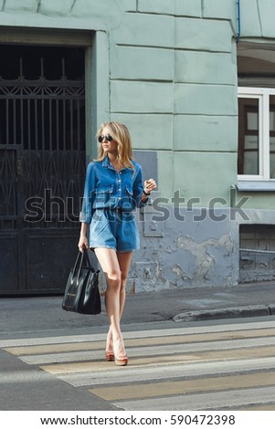 Street style. Beautiful woman walks on the street at the Moscow City at sunny spring day. #590472398