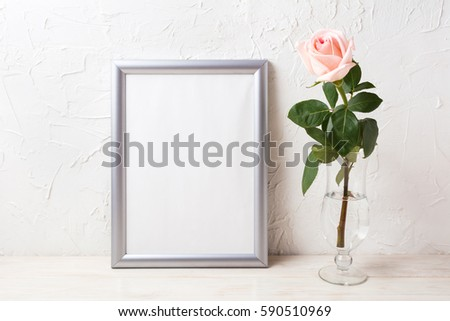 Silver frame mockup with soft pink rose in exquisite vase. Empty frame mock up for presentation artwork.