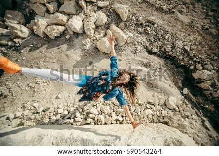 Young woman posing and dancing near the beautiful mountains dressed colorful clothes #590543264