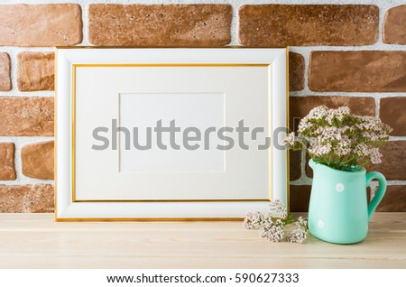 Gold decorated landscape frame mockup with wild very soft pink flowers in vase near exposed brick wall. Empty frame mock up for presentation design.  Template framing for modern art. #590627333
