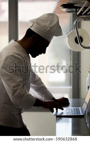 Chef using laptop on worktop #590632868