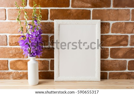 White frame mockup with purple campanula bouquet in vase near exposed brick wall. Empty frame mock up for presentation design.  Template framing for modern art. #590655317