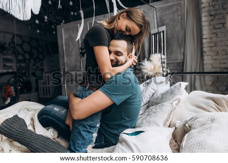 Loving couple hug each other on the bed, in big bedroom. Love story, side view Royalty-Free Stock Photo #590708636