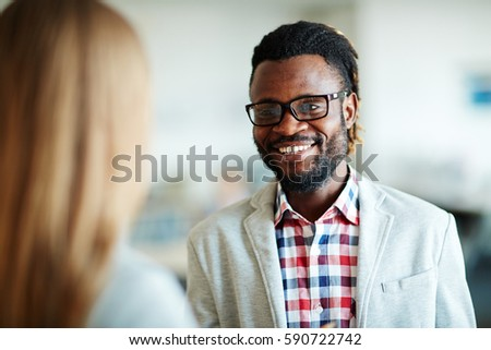 Head and shoulders portrait of cheerful bearded businessman in casualwear having conversation with his female colleague, blurred background #590722742