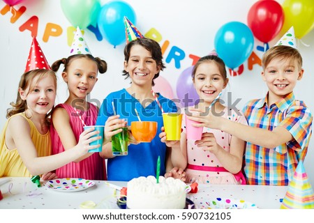 Colorful portrait of five happy kids standing together posing, holding up their drinks in celebration of birthday, looking at camera and smiling #590732105