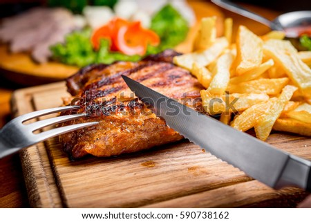 Beef steak with pepper sauce and Grilled vegetables on cutting board on dark wooden background #590738162