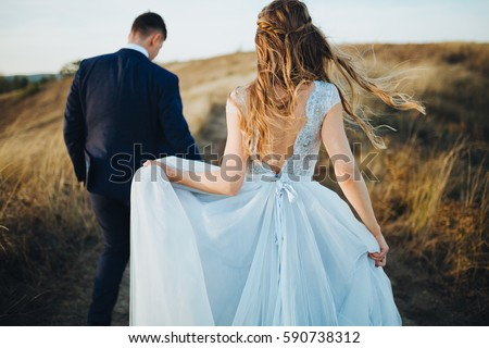 groom and bride in a wedding dress going through the field on a background of blue sky at sunset #590738312