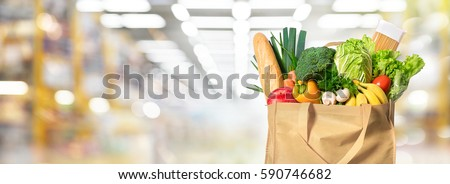 Eco friendly reusable shopping bag filled with vegetables on a blur background Royalty-Free Stock Photo #590746682