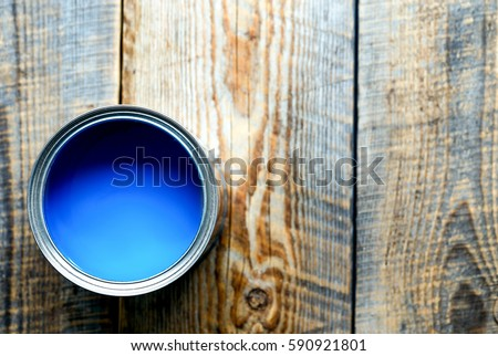 Bank with blue paint standing on wooden boards top view #590921801