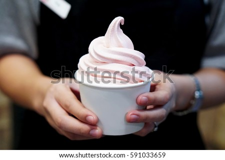 Closeup of woman's hands holding cup with organic frozen yogurt Ice cream served in a plastic takeaway, Healthy eating concept. #591033659