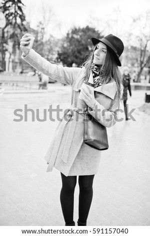 Young model girl in a gray coat and black hat with leather handbag on shoulders stay with plastic cup of coffee and making selfie at street of city. #591157040