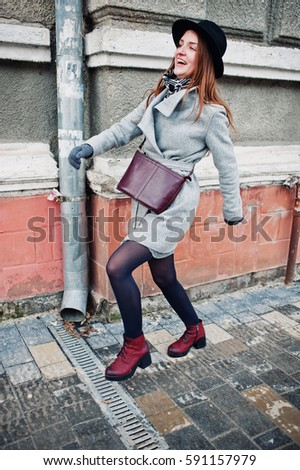 Young model girl in a gray coat and black hat with leather handbag on shoulders walking on street of city. #591157979