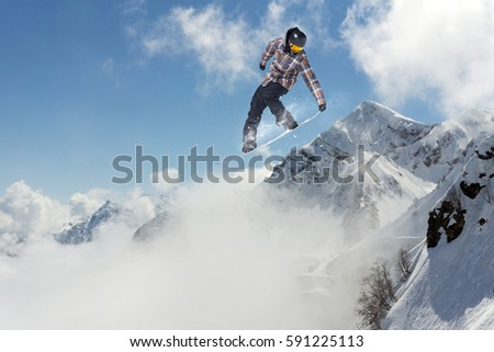 Jumping snowboarder in winter mountain. Extreme sport. #591225113