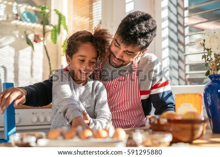 Photo of a smiling african american father and daughter baking in the kitchen and having fun. #591295880