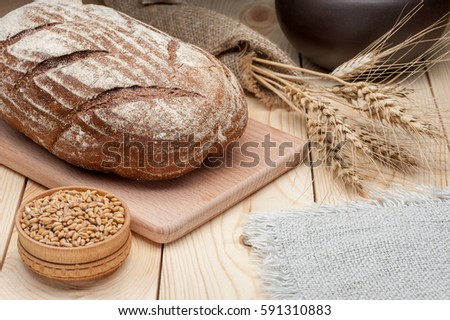 loaf of rye bread on wooden table #591310883