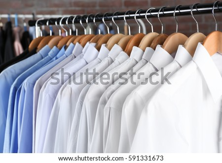 Rack of clean clothes hanging on hangers at dry-cleaning #591331673