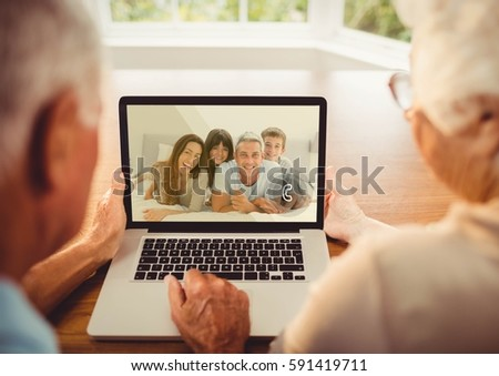 Rear view of senior couple having a video call with their family on laptop #591419711
