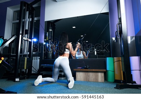 female brunette in sexy leggings and short t-shirt, doing exercises while standing in a pose of Doggy Style. in the gym #591445163