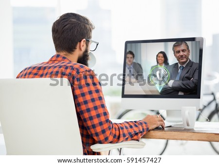 Man having video call with business people on computer at desk in office #591457427