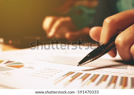 Hand woman holding pen pointing on summary report chart and calculate finance. #591470333