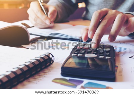 Hand man doing finances and calculate on desk about cost at home office. Royalty-Free Stock Photo #591470369
