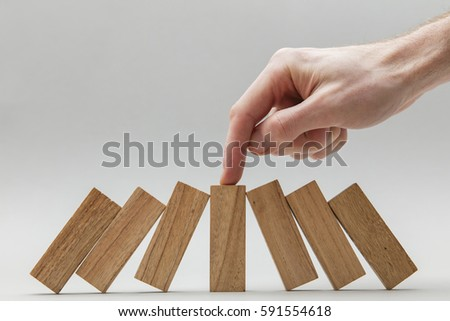 Male hand stopping wooden blocks falling over  #591554618