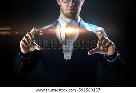 business, people, technology and cyberspace concept - close up of businessman in suit working with lightbulb projection over black background #591580157