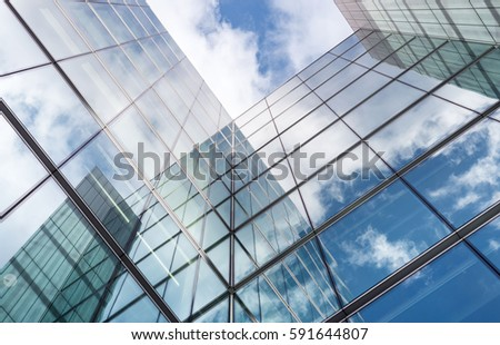 Low angle looking up at tall corporate glass buildings.  Royalty-Free Stock Photo #591644807