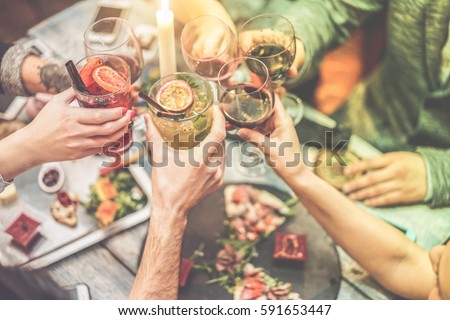 Group of friends enjoying appetizer in american bar - Young people hands cheering with wine and tropical fruits cocktails - Radial purple and green filters editing - Focus on left hands glasses Royalty-Free Stock Photo #591653447